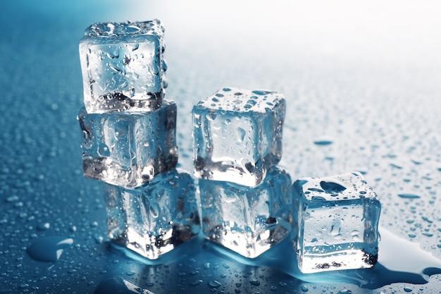 Cubetti di ghiaccio che si sciolgono messi come scale con gocce intorno, primo piano