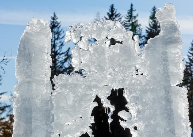 Lo scioglimento della figura del ghiaccio con il primo piano dei ghiaccioli sullo sfondo degli abeti.