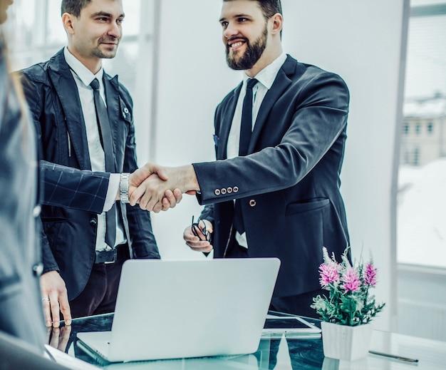 I membri del team aziendale e la stretta di mano del manager e del cliente prima della conclusione del contratto in un ufficio moderno.