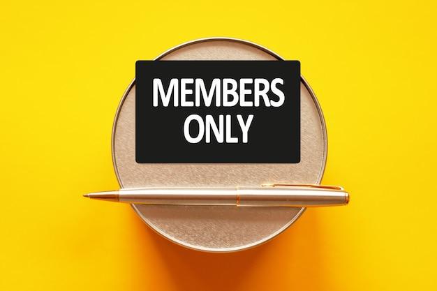 Solo per i membri- parole che scrivono lettere bianche su un foglio di carta. cartoncino nero con testo su una parete gialla con supporto rotondo in metallo e pennarello in metallo. concetto di affari, finanza e istruzione