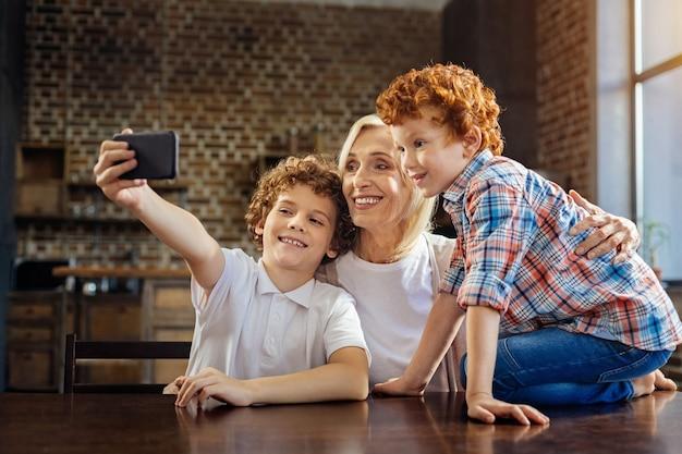 Momento memorabile. vista laterale su una famiglia felice che si incontra a un tavolo da pranzo e sorride ampiamente mentre scatta una foto di autoritratto su uno smartphone.