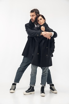 Creazione di memoria. coppia alla moda alla moda isolata su sfondo bianco studio. donna e uomo caucasici che posano in vestiti alla moda neri minimi di base. concetto di relazioni, moda, bellezza, amore.