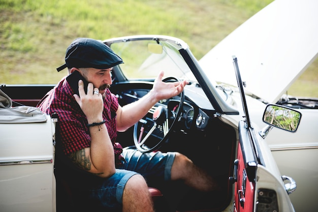 Men calling mechanic for broke down car on street side con cofano aperto