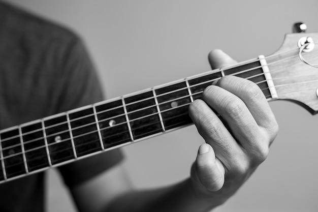 Gli uomini prendono accordi stanno imparando a suonare la chitarra. i musicisti del primo piano stanno catturando gli accordi della chitarra. i musicisti maschi tengono gli accordi e la chitarra strimpellata.