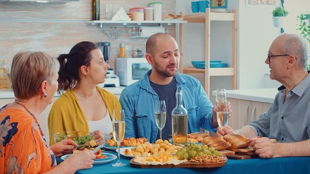 Uomini che fanno clic e discutono durante la cena. multi generazione, quattro persone, due coppie felici che parlano e mangiano durante un pasto gourmet, godendosi il tempo a casa, in cucina seduti al tavolo.