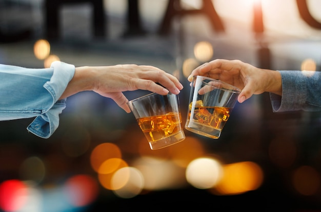 Gli uomini tintinnano insieme bicchieri di whisky