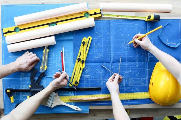 Disegnatori uomini sul tavolo disegnare progetto di costruzione
