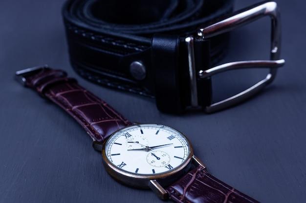 Moda uomo e accessori, orologio da polso con cinturino in pelle nera su sfondo nero