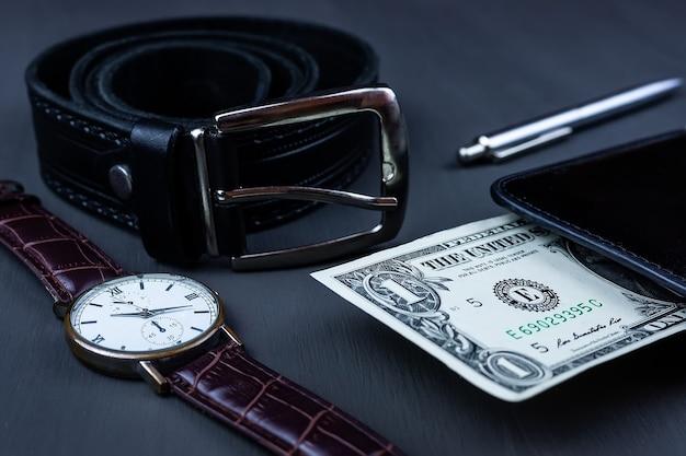 Moda uomo e accessori, orologio da polso con cinturino in pelle nera con una penna a sfera e un dollaro nel mio portafoglio su sfondo nero