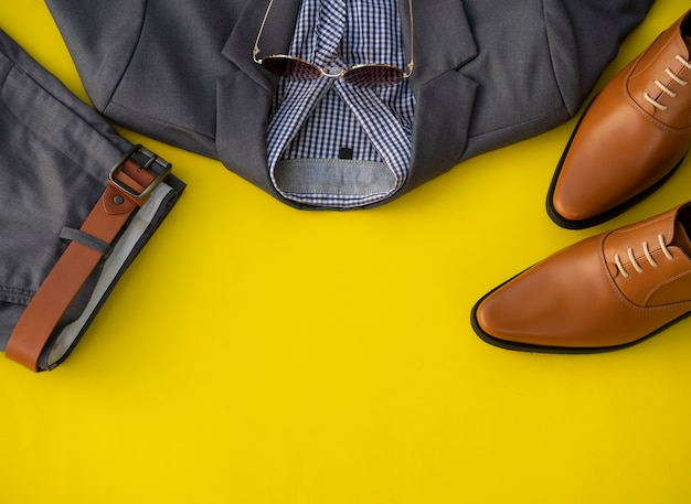 Gli uomini adattano l'insieme e gli accessori dell'abbigliamento isolati su un fondo giallo. concetto di vestiti uomo d'affari