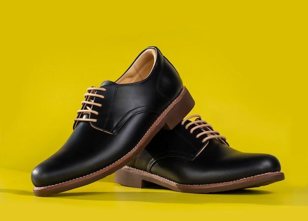 Gli uomini adattano le scarpe di cuoio del derby isolate su giallo.