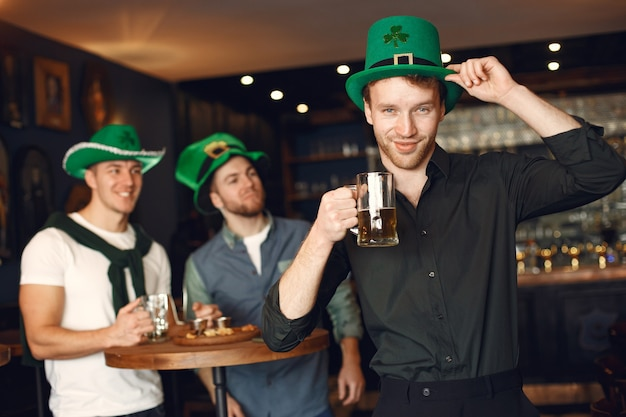 Uomini con cappelli verdi. gli amici celebrano il giorno di san patrizio. celebrazione in un pub.