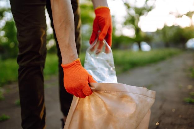 La mano degli uomini raccoglie i rifiuti di plastica per la pulizia nel parco. il volontario che indossa guanti protettivi raccoglie la bottiglia di plastica.