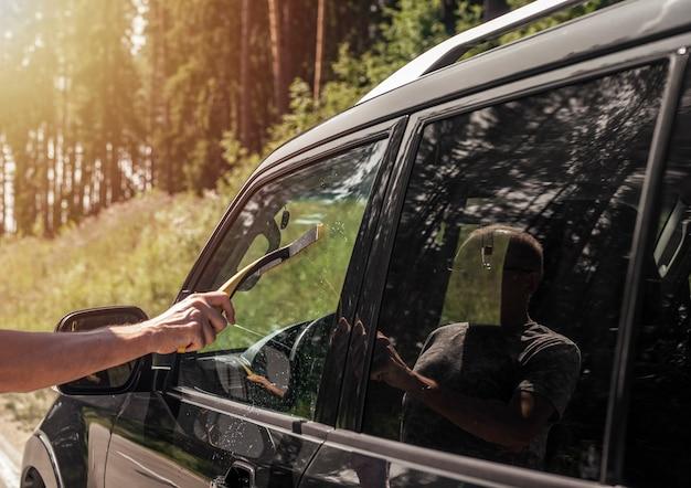 Mano degli uomini con il detergente per tergicristalli in gomma per auto che pulisce il finestrino dell'auto all'aperto