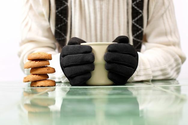 Mani degli uomini in guanti neri con una tazza di tè e biscotti