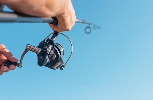 Mani degli uomini che tengono la canna da pesca volante o il pescatore sopra il cielo blu chiaro