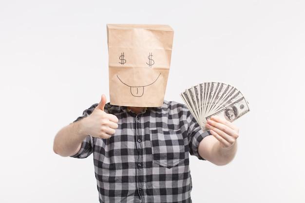 Uomini in maschera di sacchetto di carta felice con banconote di carta che mostrano i pollici in su su sfondo bianco