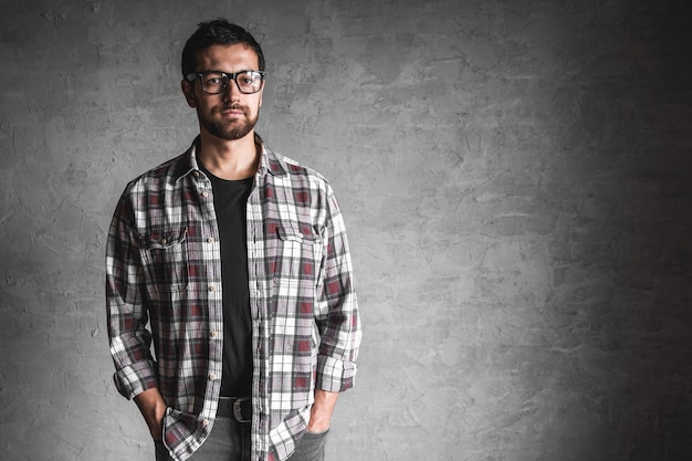 Uomini in una camicia a quadri su uno sfondo di muro di cemento grigio.