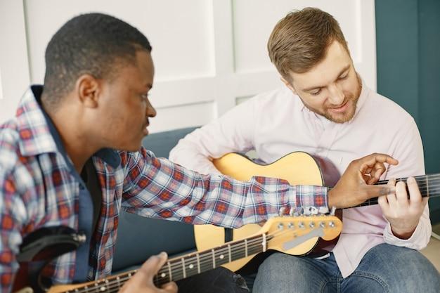 Gli uomini suonano la chitarra. scrivere musica. uomini africani e caucasici.