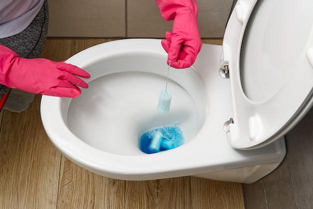 Uomini in guanti rossi che puliscono il concetto di pulizia della casa della ciotola del gabinetto