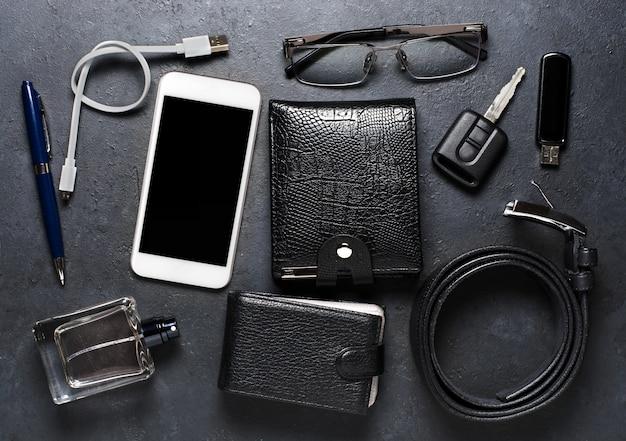 Accessori da uomo su uno sfondo di cemento nero. concetto di un uomo moderno di successo Foto Premium