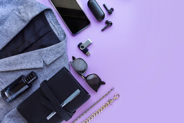 Accessori da uomo, taccuino, airpod, occhiali da sole, modello di auto su sfondo lilla. vista dall'alto, piatto.