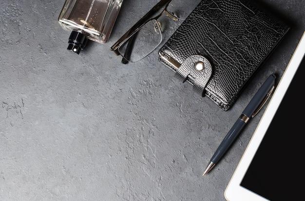 Accessori da uomo e tablet su uno sfondo di cemento nero