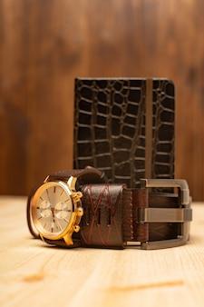 Accessori da uomo con taccuino in pelle marrone, cintura e orologio su fondo in legno