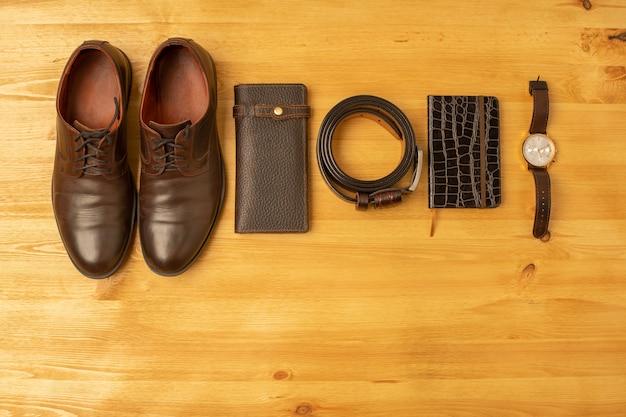 Accessori da uomo con portafoglio in pelle marrone, cintura, taccuino, scarpe e orologio su fondo in legno