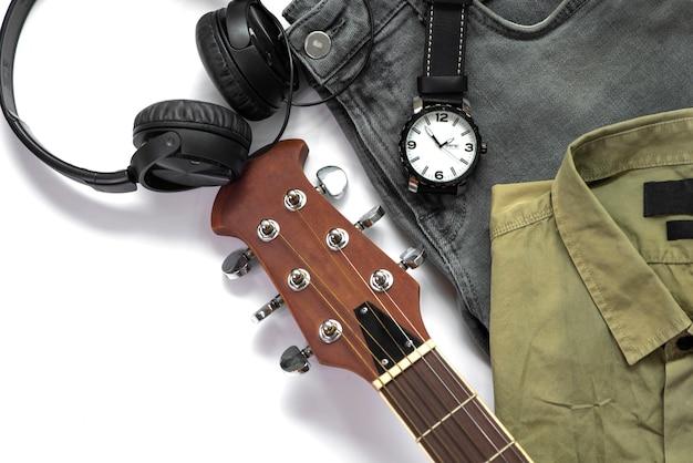 L'abbigliamento casual degli uomini per l'abbigliamento dell'uomo con la chitarra, i jeans, l'orologio, l'auricolare e la camicia isolati su fondo bianco, vista superiore.