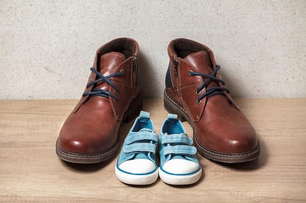 Scarpe da uomo e da bambino su un pavimento di legno
