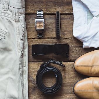 Abiti da uomo e accessori su tavola di legno. vista dall'alto
