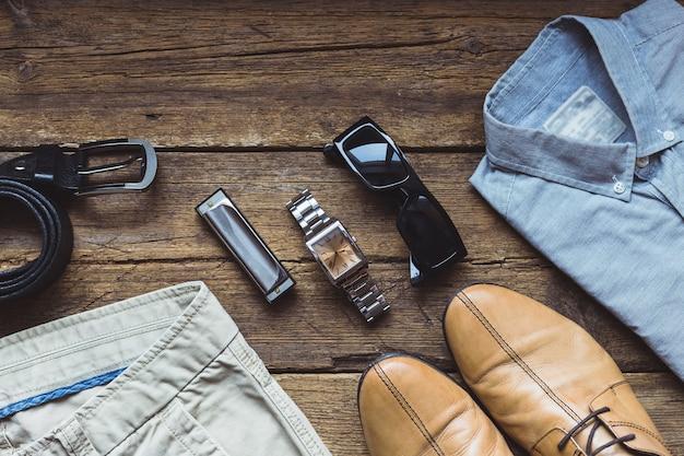 Abiti da uomo e accessori sulla tavola di legno. vista dall'alto