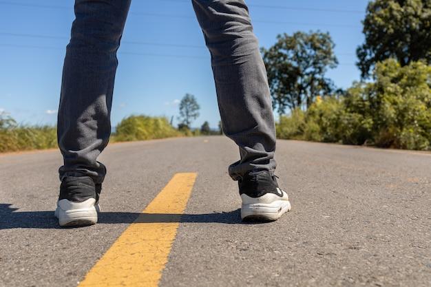 I piedi degli uomini in piedi su una strada asfaltata con linee di marcatura gialle uomo che indossa scarpe da ginnastica e jeans.