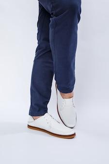 Piedi da uomo in sneakers bianche da tutti i giorni realizzate in pelle naturale su allacciatura. foto di alta qualità Foto Premium