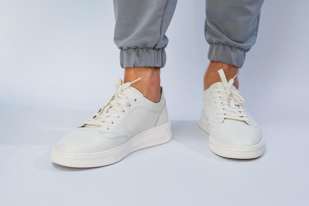 Piedi da uomo in sneakers bianche da tutti i giorni realizzate in pelle naturale su allacciatura. foto di alta qualità