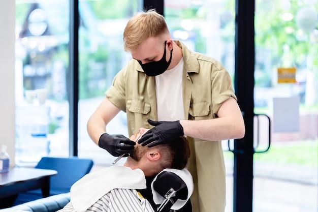 Taglio di capelli maschile in un negozio di barbiere. cliente e barbiere con maschere anti-virus. taglio di capelli in quarantena.