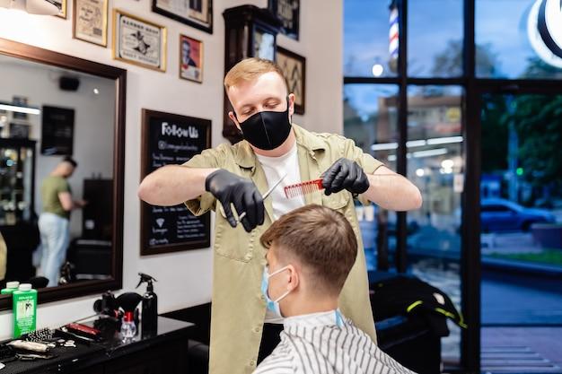 Taglio di capelli maschile in un negozio di barbiere. cura dei capelli. barbiere e cliente in maschera contro il virus. taglio di capelli in