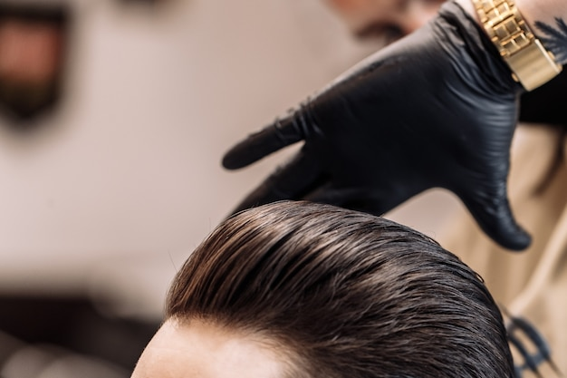 Taglio di capelli maschile in un barbiere. styling e cura dei capelli. salone di bellezza.