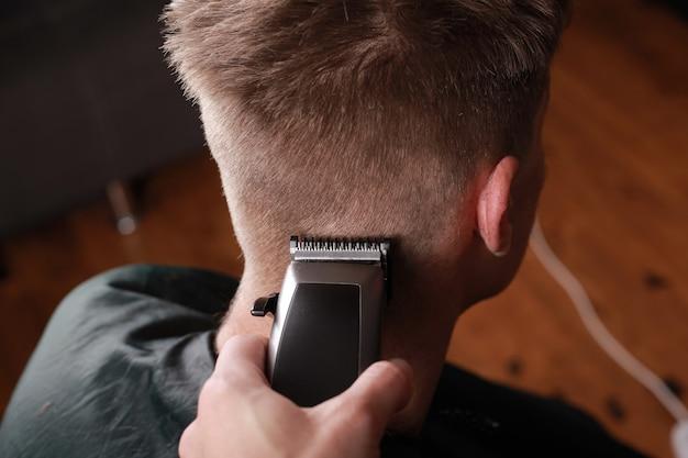 Taglio di capelli maschile, il maestro taglia il ragazzo con un tagliacapelli, uno strumento da parrucchiere.