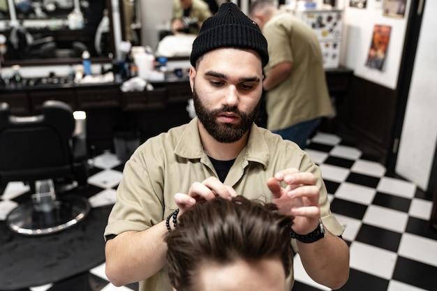 Taglio di capelli da uomo. il parrucchiere alla moda taglia un uomo. stile maschile