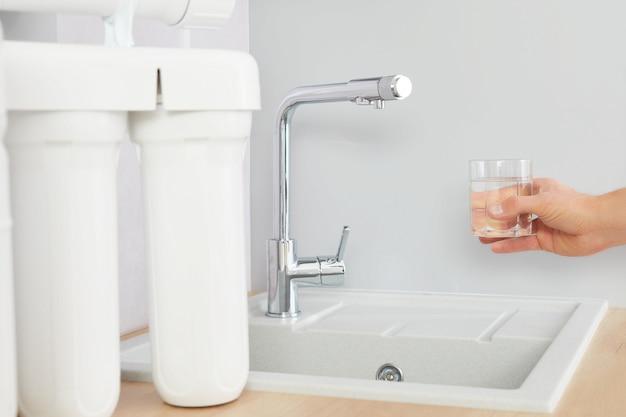 La mano degli uomini tiene un bicchiere di acqua limpida. tocca e il filtro dell'osmosi inversa in background.