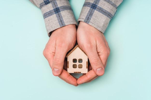 Le mani degli uomini abbracciano una casa in legno come simbolo di cura