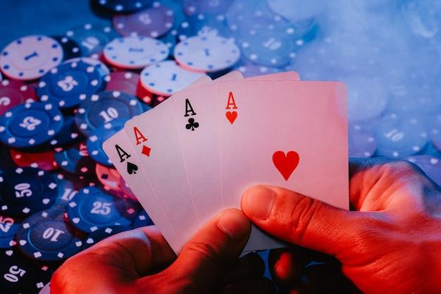 Le mani degli uomini tengono le carte degli assi sullo sfondo delle fiches. la foto mostra fumo