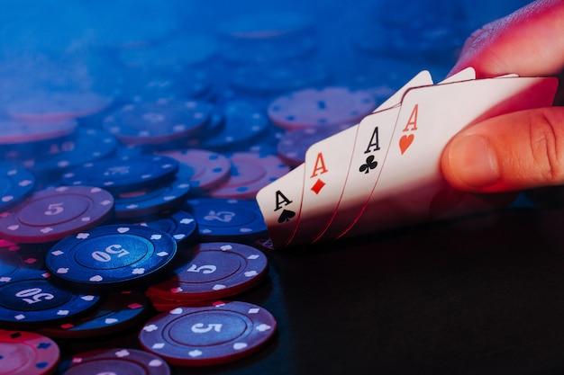 Le mani degli uomini tengono le carte sullo sfondo del gioco delle fiches. c'è del fumo nella foto