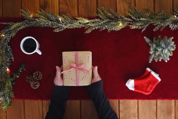 Le mani degli uomini tengono un regalo di natale in laici piana con un tavolo di legno