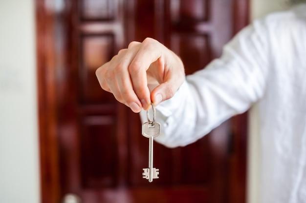 Le mani degli uomini tengono la chiave di casa su uno sfondo di porta di legno. possedere il concetto immobiliare