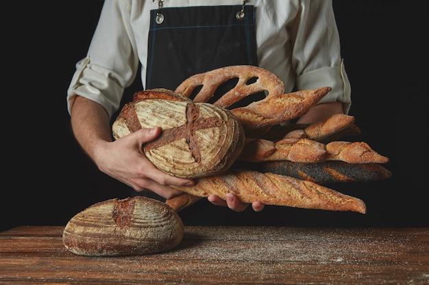 Le mani degli uomini tengono molti pani diversi su un tavolo di legno