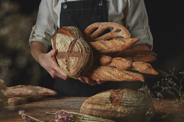 Le mani degli uomini tengono una varietà di pane sullo sfondo nero di un tavolo di legno con fiori secchi