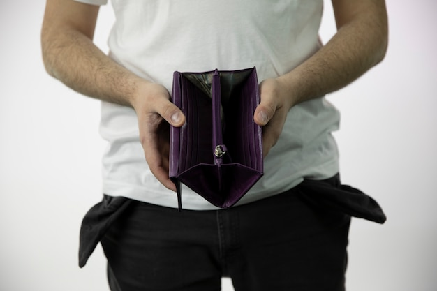 Le mani degli uomini mostrano un portafoglio aperto vuoto e tasche vuote dei pantaloni rovesciate